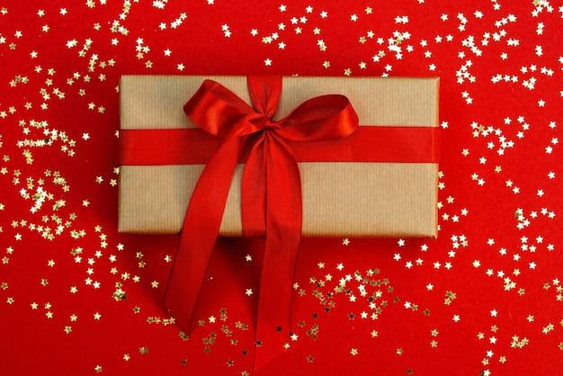 クリスマスのミニマルな構成。赤い背景に輝く星が付いたサテンのリボンが付いたギフトクラフトボックス。フラットレイ、上面図