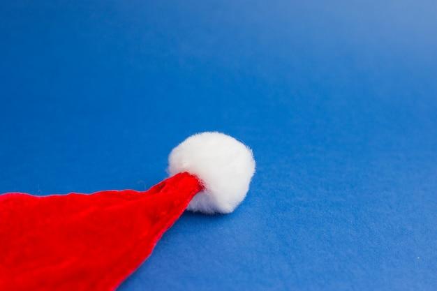 クリスマスのミニマルな構成。青いトレンドの背景にサンタの帽子。今年の色。フラットレイスタイル。上面図。