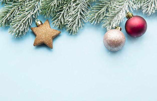 クリスマスのミニマルコンセプト-雪に覆われたモミの枝とつまらないものとクリスマスの構成
