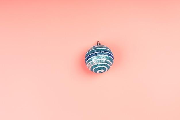 クリスマスのミニマルな背景。ピンクの背景にクリスマスボール。シルバーラメのクリスマスのおもちゃ。上面図、フラットスタイル