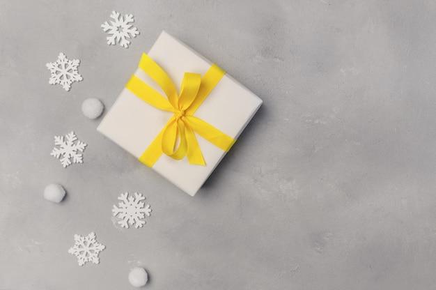 クリスマスは、テキストの場所と木製の背景に雪片とギフトボックスで背景をモックアップします。