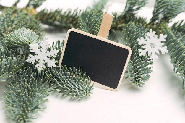 녹색 전나무 가지, 원뿔, 눈송이의 흰색 나무 장식이 있는 크리스마스 모형 구성.