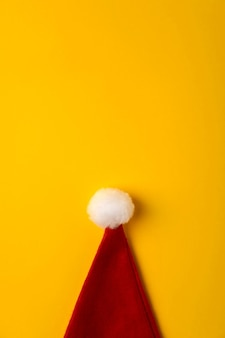 Christmas modern composition. santa hat on yellow background.