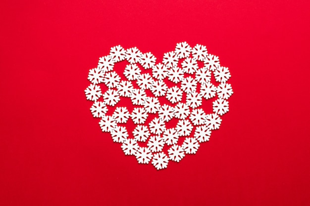 Christmas modern composition. xmas snow heart decorations on red background