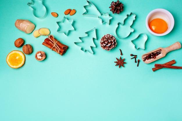 青い背景にジンジャーブレッドクッキーを作るためのクリスマスの型。フラットレイスタイル