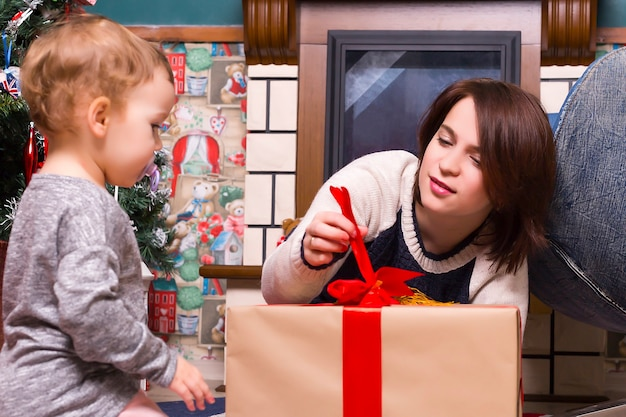Christmas, mom and daughter open a gifts at home