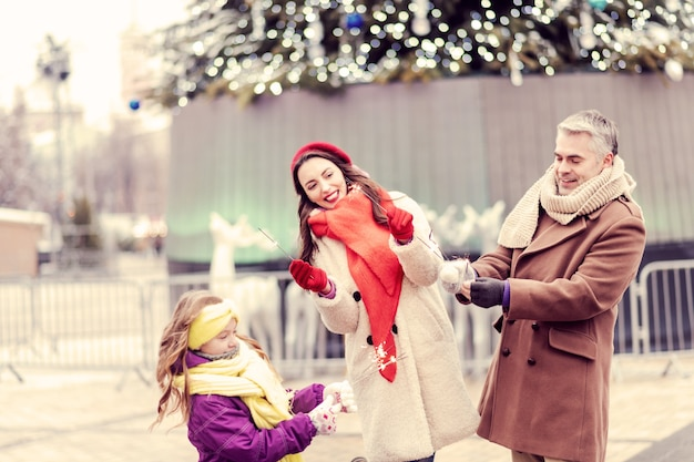 크리스마스 분위기. 크리스마스 트리 근처를 걷고 카메라에 포즈를 취하는 긍정적 인 기쁘게 사람들