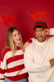 크리스마스 분위기. 빨간 배경에 뿔이 있는 모자를 쓴 두 젊은이