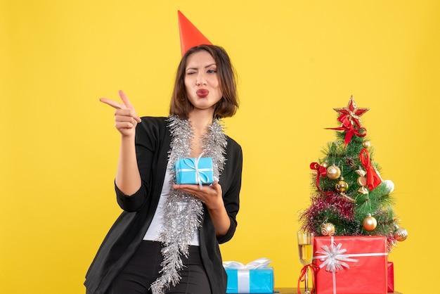 Atmosfera natalizia con una bella signora che tiene il regalo che indica qualcosa in ufficio su giallo