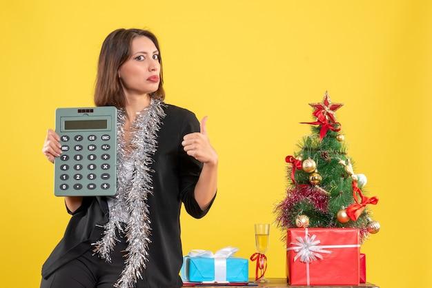 Atmosfera natalizia con bella signora in piedi in ufficio e calcolatrice di puntamento che fa il gesto giusto in ufficio su giallo