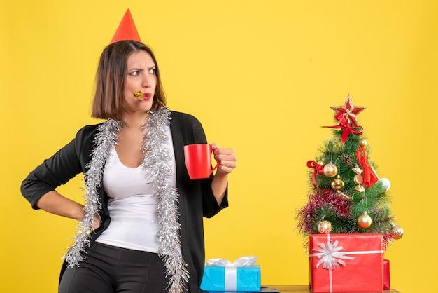 Atmosfera natalizia con bella signora confusa che tiene la tazza rossa in ufficio su giallo