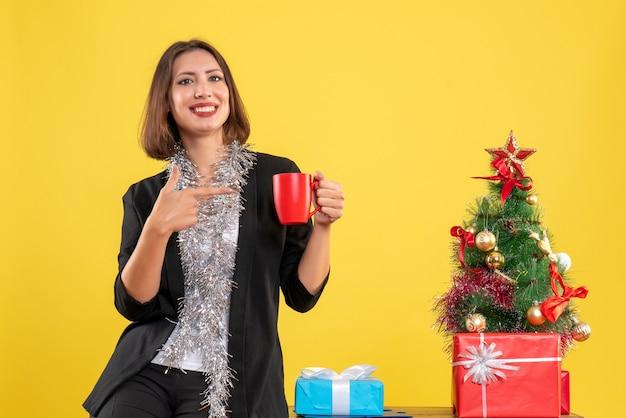 Atmosfera natalizia con bella signora emotiva in piedi in ufficio e indicando la tazza rossa in ufficio su giallo