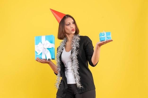 Рождественское настроение с эмоциональной бизнес-леди в костюме с рождественской шляпой, смотрящей на свои подарки на желтом