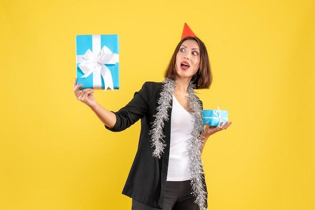 Atmosfera natalizia con signora emotiva di affari con il cappello di natale che tiene i regali su giallo