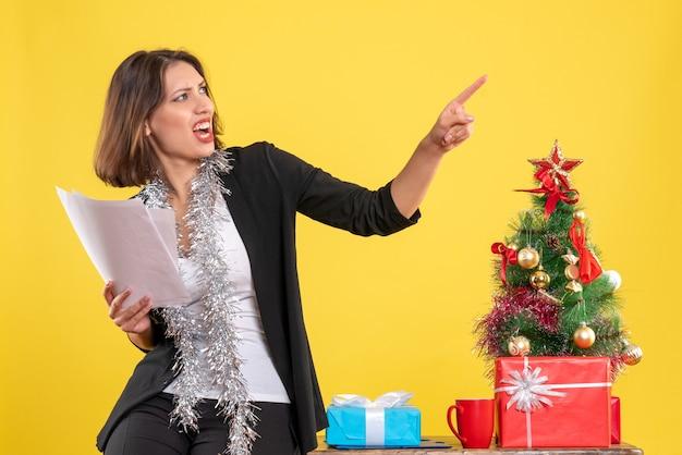 Atmosfera natalizia con bella signora nervosa emotiva in piedi in ufficio e in possesso di documenti in ufficio su giallo