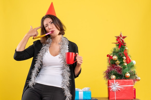 Christmas mood with funny beautiful lady holding the red cup in the office on yellow