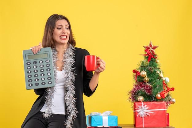 Atmosfera natalizia con bella signora nervosa in piedi in ufficio e tenendo la tazza calcolatrice in ufficio su giallo