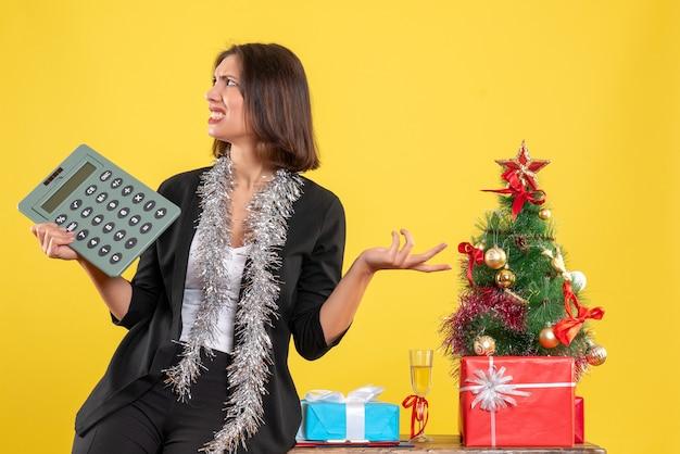Atmosfera natalizia con bella signora nervosa in piedi in ufficio e tenendo la calcolatrice in ufficio su giallo