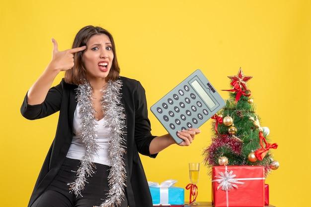 Рождественское настроение с нервной растерянной красивой дамой, стоящей в офисе и держащей калькулятор в офисе на желтом