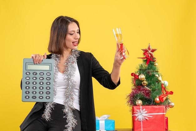 긍정적 인 아름다운 아가씨가 사무실에 서서 노란색에 사무실에서 와인을 올리는 계산기를 들고 크리스마스 분위기