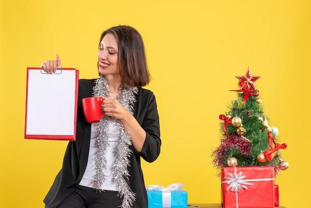 ポジティブな美しい女性がオフィスに立って、黄色のオフィスでドキュメントカップを保持しているクリスマス気分