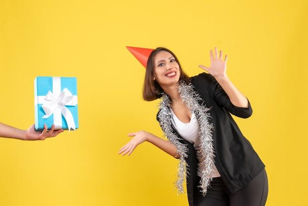 Atmosfera natalizia con signora positiva di affari in vestito con cappello di natale e regalo della holding della mano su giallo