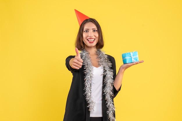 Atmosfera natalizia con signora positiva di affari in vestito con cappello di natale e regalo della holding che fa gesto giusto su colore giallo
