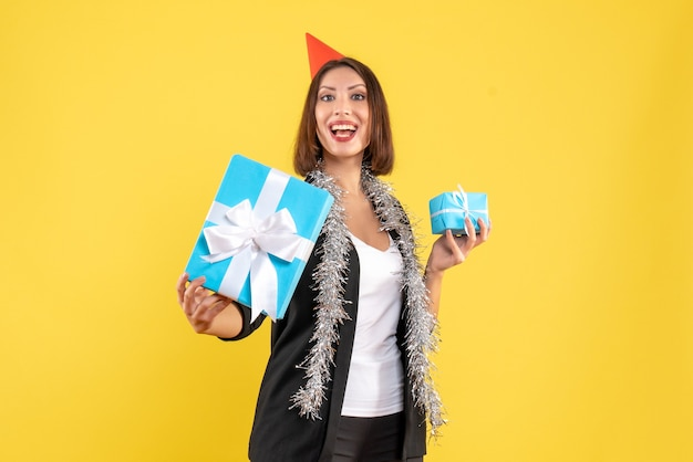 Christmas mood with proud business lady in suit with xsmas hat showing her gift on yellow