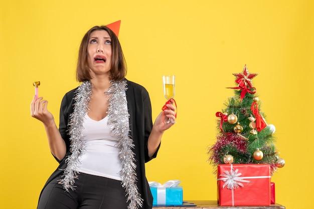 Atmosfera natalizia con bella signora spaventata che tiene il vino e alzando lo sguardo in ufficio sul giallo