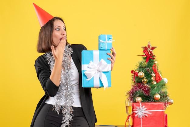 Atmosfera natalizia con bella signora scioccata con cappello di natale che tiene i regali in ufficio su giallo