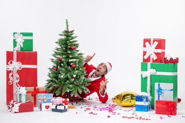 Atmosfera natalizia con babbo natale scioccato che si nasconde dietro l'albero di natale vicino a regali in diversi colori su sfondo bianco