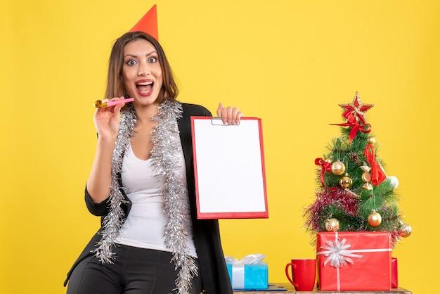 Atmosfera natalizia con sorridente bella signora che tiene il documento in ufficio su giallo