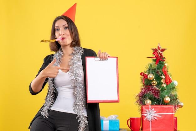Atmosfera natalizia con sorridente bella signora che tiene il documento che indica se stessa in ufficio su giallo