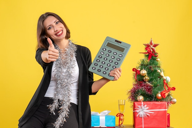 Christmas mood with smiling beautiful lady standing in the office and pointing calculator making ok gesture in the office on yellow