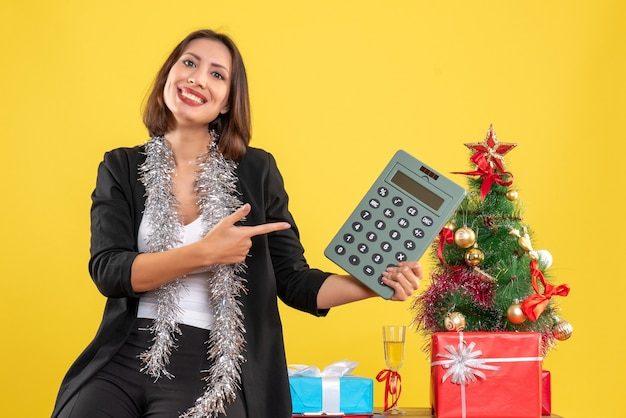Christmas mood with smiling beautiful lady standing in the office and pointing calculator in the office on yellow