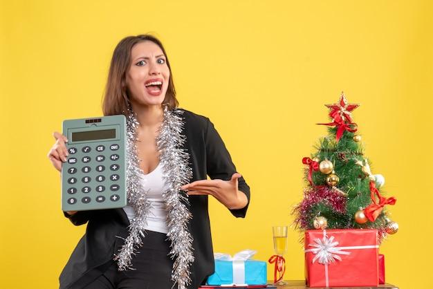 Atmosfera natalizia con sorridente bella signora in piedi in ufficio e indicando la calcolatrice in ufficio su giallo