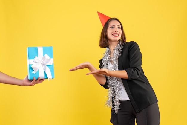 Atmosfera natalizia con sorridente donna d'affari in tuta con cappello di natale che punta la mano che tiene il regalo su giallo