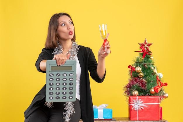 オフィスに立って、黄色のオフィスでワインを上げる電卓を持っている驚きの美しい女性とクリスマス気分