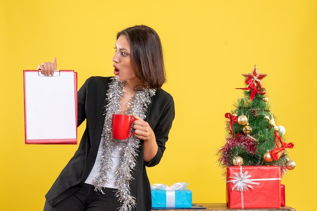 Christmas mood with surprised beautiful lady standing in the office and holding documents cup in the office on yellow