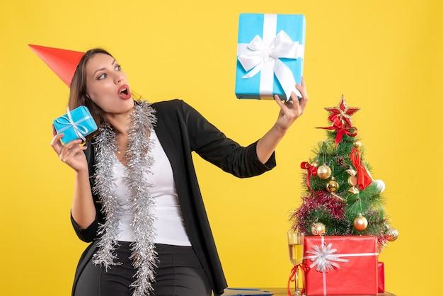 Atmosfera natalizia con bella signora sorpresa con il cappello di natale che tiene i regali in ufficio su giallo