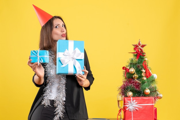 Atmosfera natalizia con bella signora positiva sorpresa con il regalo della holding del cappello di natale nell'ufficio su colore giallo