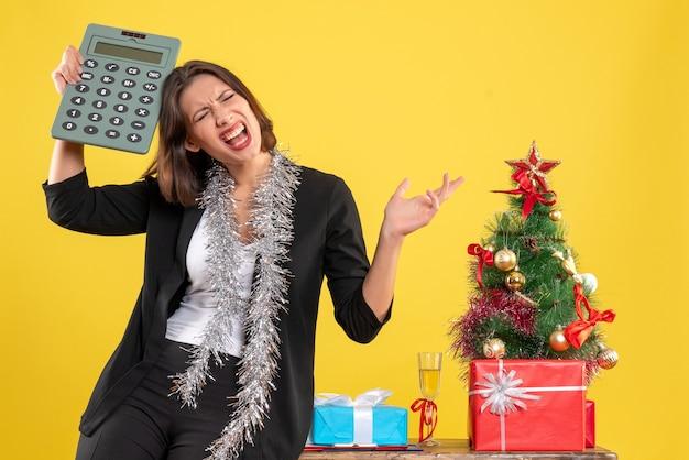 緊張した美しい女性がオフィスに立って、黄色のオフィスで電卓を保持しているクリスマス気分