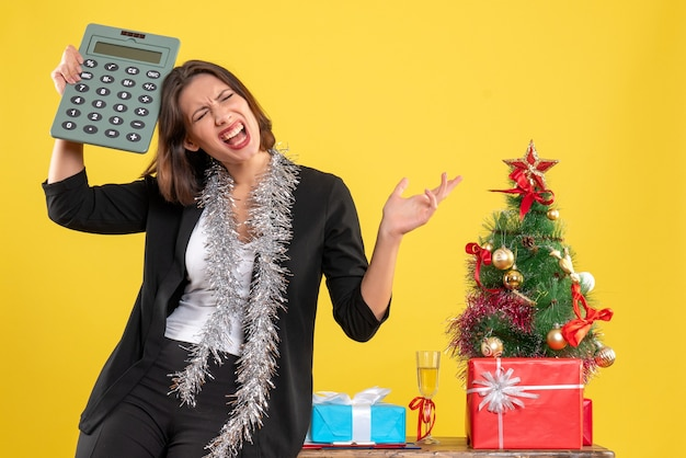 Christmas mood with tense beautiful lady standing in the office and holding calculator in the office on yellow