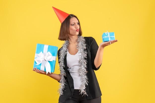 Atmosfera natalizia con donna d'affari incerta in tuta con cappello di natale che mostra il suo regalo su giallo