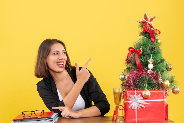 Atmosfera natalizia con la giovane donna di affari che indica qualcosa sul giallo