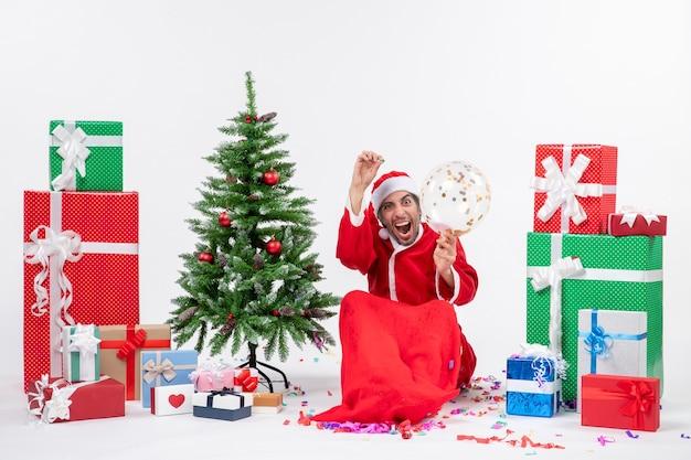 クリスマスツリーの近くに座っている若い幸せなクレイジーハサンタクロースと白い背景の上のさまざまな色の贈り物とクリスマス気分