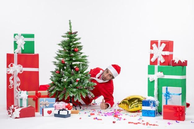 Atmosfera natalizia con il giovane babbo natale che si nasconde dietro l'albero di natale vicino a regali in diversi colori su sfondo bianco stock photo