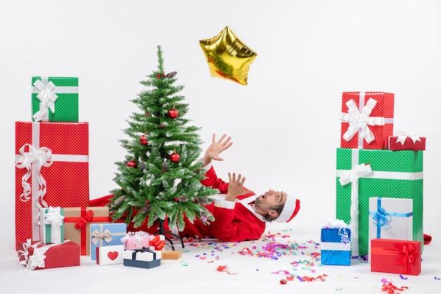 Рождественское настроение с молодым санта-клаусом, лежащим за елкой возле подарков разных цветов на белом фоне stock photo