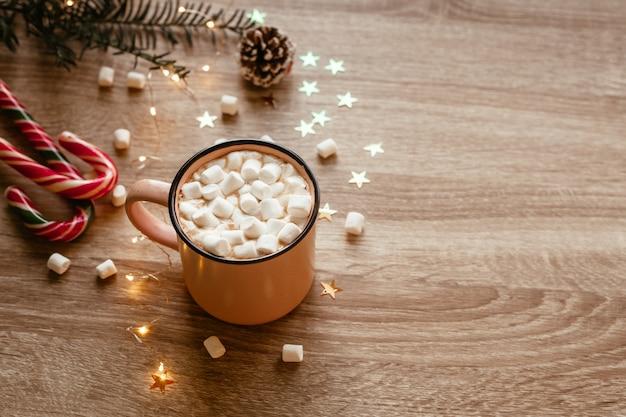 マシュマロと紙吹雪のコーヒーのピンクのカップとクリスマスの不機嫌そうな写真
