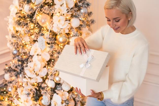 집에서 크리스마스 아침: 새해 전날 크리스마스 트리에 앉아 있는 행복한 젊은 여성이 선물 상자를 엽니다.